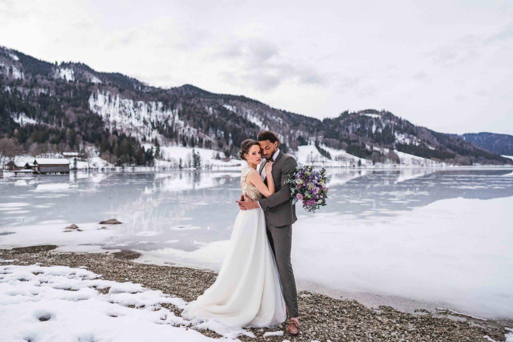 Winterhochzeit Brautpaar Brautkleid Schnee See Blumenstrauß Brautstrauß Hochzeit Hochzeitskarten Heiraten im Winter Schliersee Bayern Bayernhochzeit Alpen Allgäu